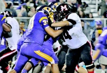 Robert Parrie (44) attempts to fight off Oakdale fullback Timmy Townley (33) during action last Friday night. Parrie and the Many Tigers blanked Townley and the Warriors, 42-0. (Special to the Index/TINA McCORMIC)